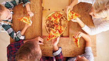 perhe syömässä pitsaa