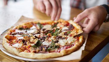 mies syö pitsaa lautaselta pizza pizzalautanen