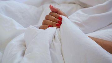 naisen käsi sängyssä