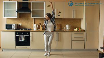 Nuori nainen relaa keittiössä / Asuntomessut