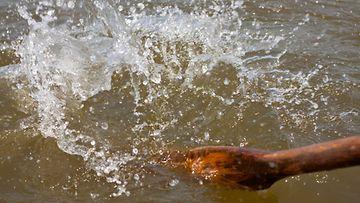 Soutuveneen airo läiskyttää vettä, kuvituskuva