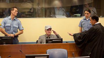 Ratko Mladic teki sotilastervehdyksen istuutuessaan syytetyn penkille Haagissa.