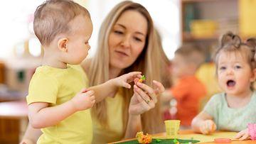 Nainen ja lapsia päivähoidossa, leikkii