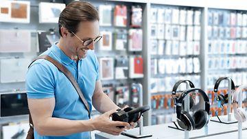 Mies ostoksilla elektroniikkaliikkeessä