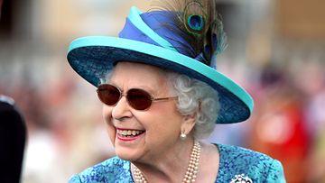 kuningatar Elisabet aurinkolasit päässä