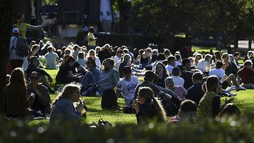 Kouluvuoden päätöksen juhlintaa kauniissa auringonpaisteessa Esplanadin puistossa Helsingissä alkuillasta