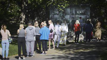 LEHTIKUVA: Kouluvuoden päätöksen juhlijoita vessajonossa pitäen turvaväliä kauniissa auringonpaisteessa Kaivopuistossa Helsingissä alkuillasta 30. toukokuuta 2020.