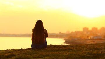 tyttö istuu rannalla