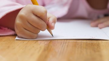 shutterstock pikkutyttö tekee läksyjä