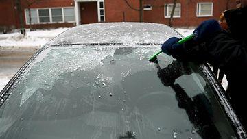 LK 23.2.2021 Mies puhdistaa auton tuulilasia jäästä Helsingissä 22. helmikuuta 2021.