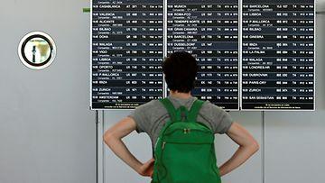 Mies katselee lähtevien lentojen listaa Madridin lentokentällä.