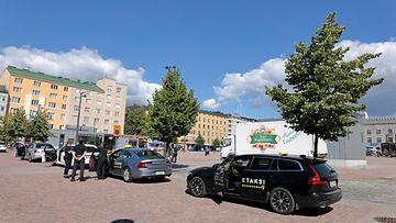 Takseja jonossa Lahden torin taksitolpalla kirkkaana kesäpäivänä.