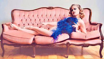 Burleskitaiteilija Goldie Starlett vaaleanpunaisen sohvan päällä.