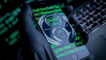 hakkeri pitelee älypuhelinta rikollinen puhelin 26.06906454