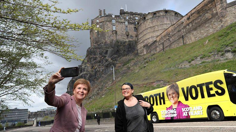 Skotlannin pääministeri Nicola Sturgeon ottaa selfie-kuvaa kannattajansa kanssa Edinburghin linnan edustalla.
