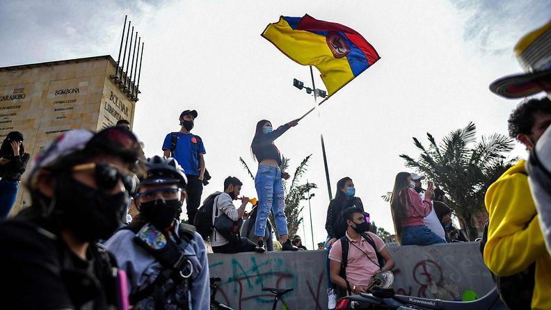 Nainen heiluttaa Kolumbian lippua protesteissa presidenttiä vastaan Bogotassa.