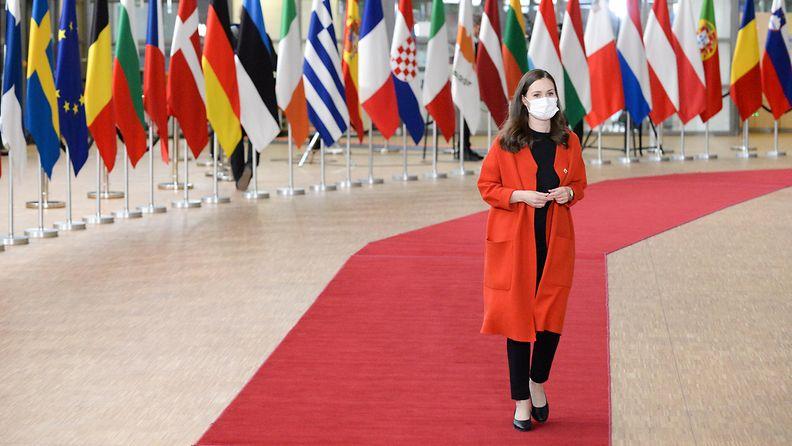 Sanna Marin EU-kokouksessa lippujen edessä.