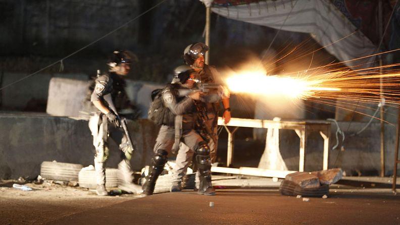 Israelin armeijan sotilaat ampuvat kyynelkaasua palestiinalaisia mielenosoittajia kohti.