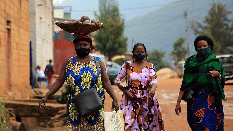Naisia kävelemässä pukeutuneina värikkäisiin mekkoihin ja kasvomaskeihin Ruandan pääkaupungissa Kigalissa huhtikuussa 2021.