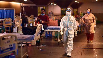 Suoja-asuun pukeutunut lääkäri kävelee koronapotilaiden hoitokeskuksessa New Delhissä.