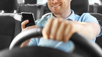 shutterstock auton ajaminen kännykkä kädessä