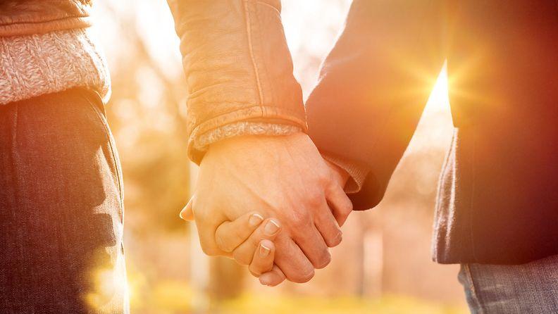 pariskunta pitää toisiaan kädestä