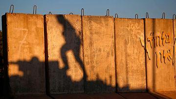 Barrikadille heijastuu israelilaisen sotilaan varjo hänen kiivetessä panssarivaunun päälle.