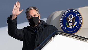 Antony Blinken tervehtii lentokoneen ovella.