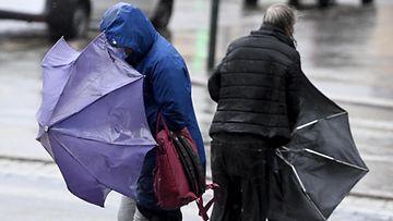 LKS 20210526 Jalankulkijat kamppailevat sateenvarjojensa kanssa tuulisessa ja sateisessa Helsingissä 26. toukokuuta 2021.