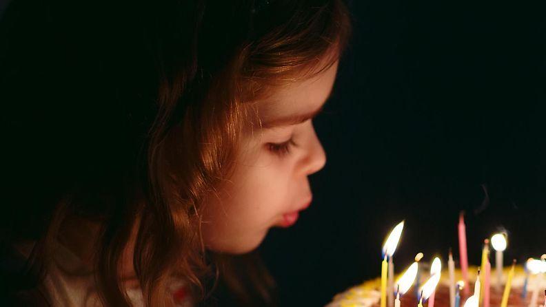 lapsi puhaltaa kynttilät
