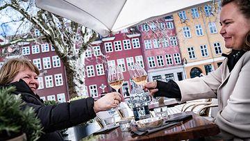 Kaksi hymyilevää asiakasta kilistämässä viinilasejaan terassilla Kööpenhaminassa.