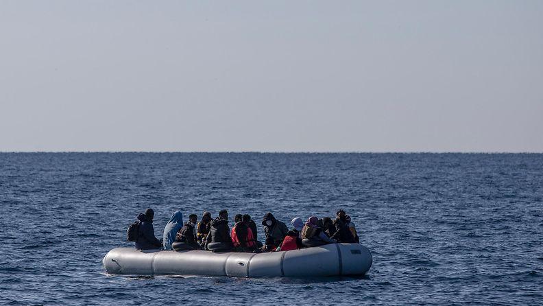 Turkin rannikkovartiosto pelastaa siirtolaisia kumiveneellä. Vene on tupaten täynnä ja ympärillä pelkkää merta.
