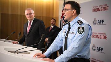 Komisario Reece Kershaw puhuu AFP:n tiedotustilaisuudessa. Australian pääministeri Scott Morrison katsoo taustalla.