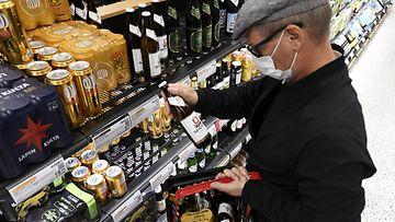 Mies ostoksilla Alkon Ruoholahden myymälässä Helsingissä.