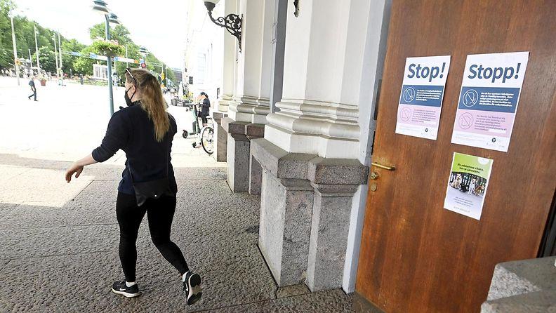 Tummiin pukeutunut nainen lähtee äänestyspaikalta Helsingin kaupungintalolta vaalipäivänä 13. kesäkuuta.