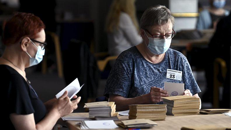 Maskeihin pukeutuneet ääntenlaskijat laskevat ennakkoääniä Finlandiatalolla Helsingissä.