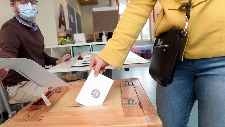 Keltaiseen takkiin pukeutunut äänestäjä laittaa lipun vaaliuurnaan Espoossa Finnoon koululla.