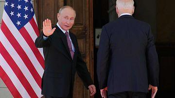 Vladimir Putin vilkuttaa taakseen kun hän astuu Joe Bidenin kanssa ovesta sisään Geneven huippukokouksessa.