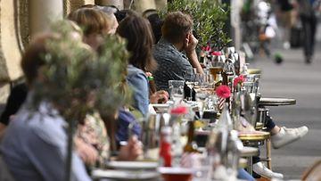 Ihmisiä nauttimassa lämpimästä säästä ravintolan terassilla Helsingissä.