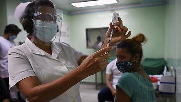 Hoitaja mittaa ruiskuun kuubalaista Abdala-rokotetta, potilaan seuratssa toimenpidettä taustalla.