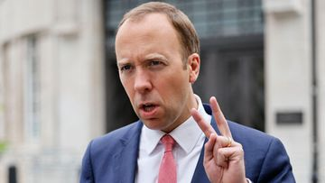 Britannian terveysministeri Matt Hancock näyttää voitonmerkkiä.