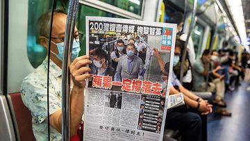 Mies lukee Apple Daily -sanomalehteä junassa Hongkongissa.