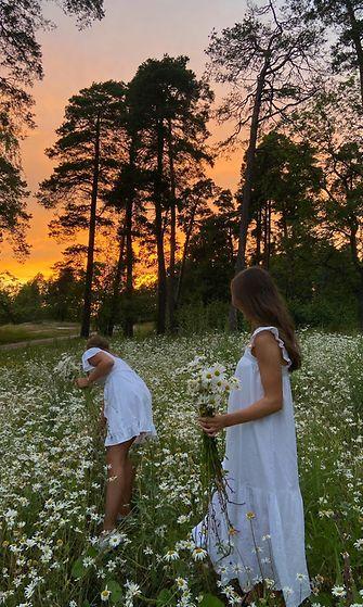 Kaksi naista poimii kukkia niityllä valkoisissa mekoissa.