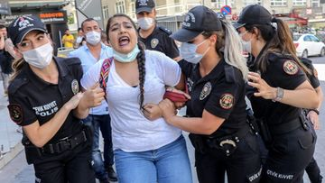 Poliisit taluttavat mielenosoitukseen osallistunutta naista.