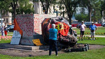 Ihmiset katsovat kaadettua Kuningatar Viktorian patsasta. Patsaan juuri on töhritty punaisessa maalissa kastetuilla kädenjäljillä.
