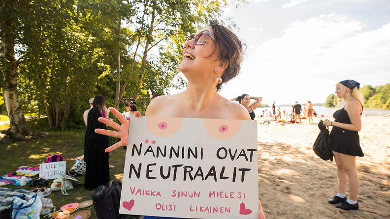 """Meri-Maija Näykki pitelee tissiflashmobissa kylttiä, johon on maalattu naisen rinnat ja teksti: """"Nännini ovat neutraalit vaikka sinun mielesi olisi likainen""""."""""""