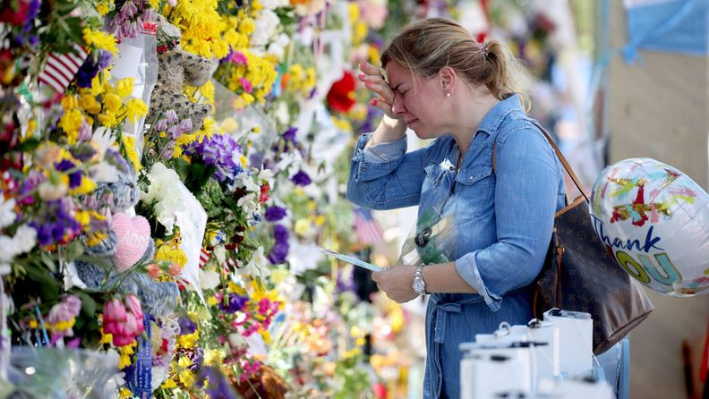 Nainen itkee Floridan romahtaneen kerrostalon muistomerkillä.