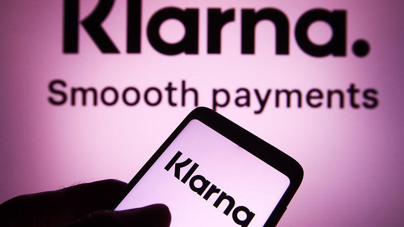 Henkilö pitää kädessään puhelinta, jonka näytöllä ja puhelimen taustalla näkyy Klarnan logo.