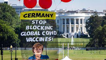 Mielenosoittajien Valkoisen talon edustalle ilmapalloilla ripustama lakana, jossa vaaditaan Merkelin tukea rokotepatenttien purkamiseen.