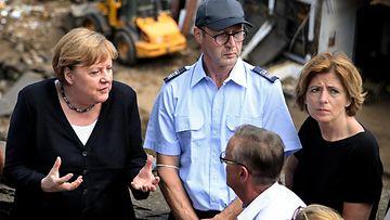 Liittokansleri Angle Merkel (vas.) puhuu miehelle vierailullaan tulva-alueella Schuldissa. Taustalla romua ja keltainen pyöräkuormaaja.